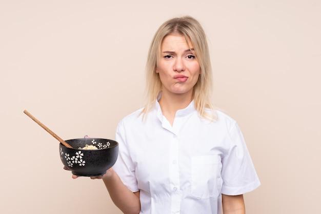 箸で麺のボウルを押しながら悲しい表情で孤立した壁の上の若いロシア人女性