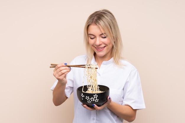 箸で麺のボウルを保持している孤立した壁の上の若いロシア人女性