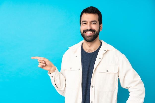 Молодой красавец с белой вельветовой курткой над синей стеной, указывая пальцем в сторону