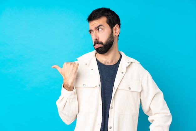 不幸と側を指している分離の青い壁に白いコーデュロイジャケットと若いハンサムな男