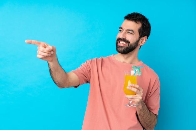 若い男が横に指を指していると分離された青い壁にカクテルを押しながら製品を提示