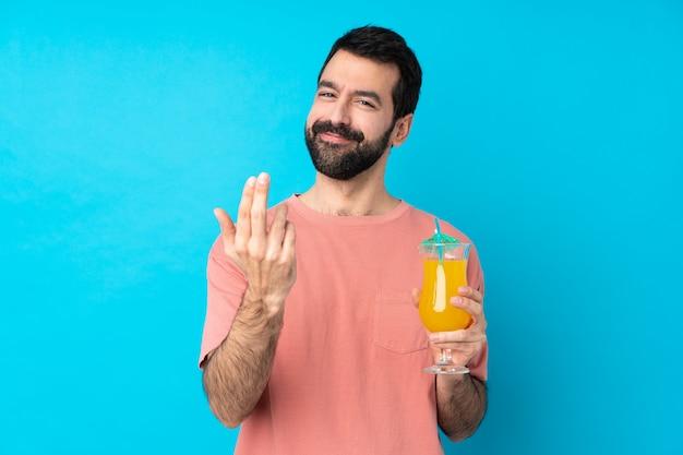 Молодой человек над держать коктеиль над изолированной голубой стеной приглашая прийти с рукой. рад, что ты пришел