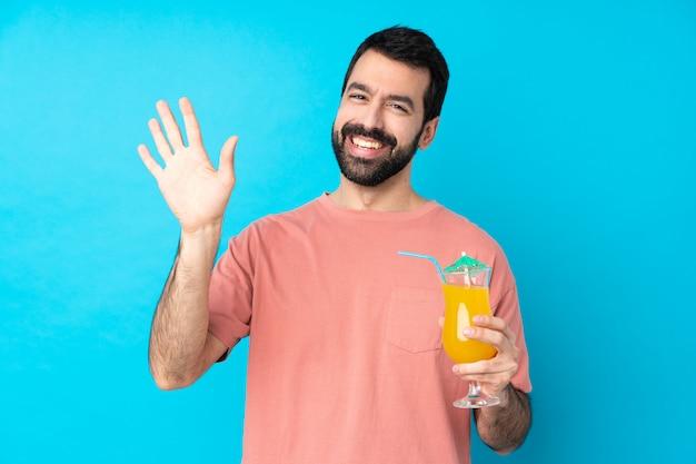 幸せな表情で手で敬礼分離の青い壁にカクテルをかざす以上の若い男
