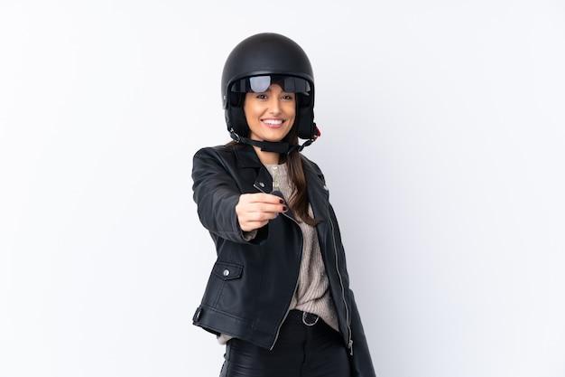 オートバイのヘルメットと分離の白い壁にキーを保持している若いブルネットの女性