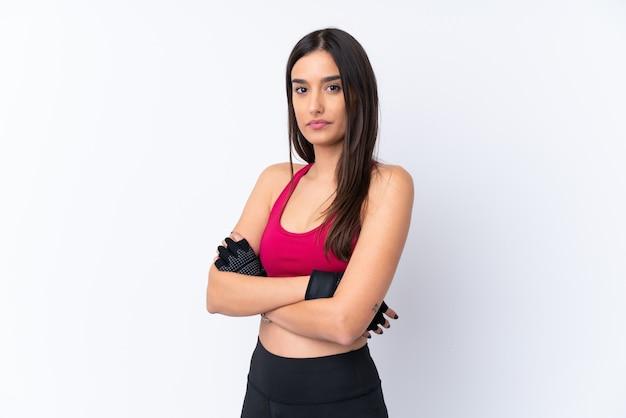Молодая женщина брюнет спорта над изолированной белой стеной держа оружия пересеченный