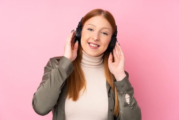 音楽を聴く分離のピンクの壁の上の若い赤毛の女性