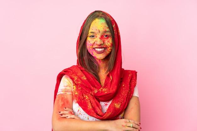 Молодая индийская женщина с красочными порошками холи на лице, изолированные на розовой стене, держа руки скрещенными в лобном положении