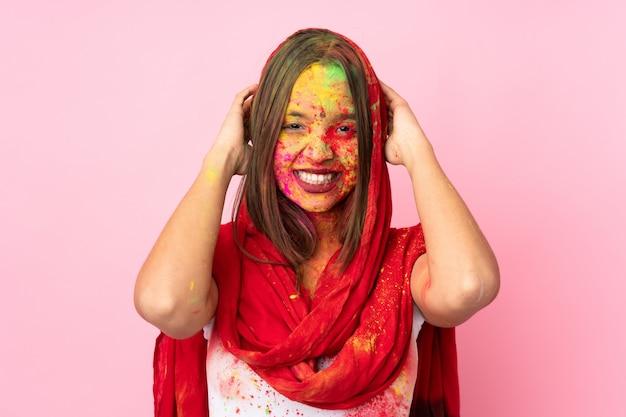 ピンクの壁の笑いに分離された彼女の顔にカラフルなホーリーパウダーを持つ若いインド人女性