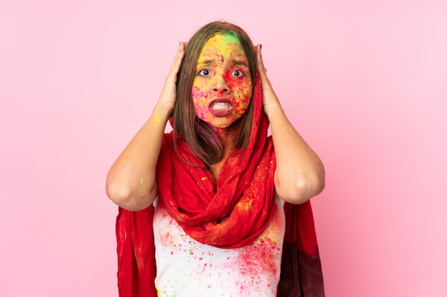 緊張のジェスチャーをしているピンクの壁に分離された彼女の顔にカラフルなホーリーパウダーを持つ若いインド人女性