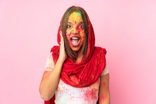 Молодая индийская женщина с красочными порошками холи на лице, изолированные на розовой стене с удивлением и шокирован выражением лица