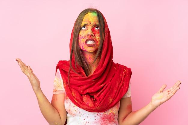 ピンクの壁に分離された彼女の顔にカラフルなホーリーパウダーを持つ若いインド人女性が圧倒されると強調