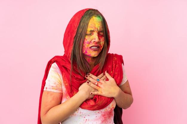 心の痛みを持っているピンクの壁に分離された彼女の顔にカラフルなホーリーパウダーを持つ若いインド人女性