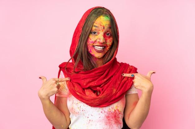 ジェスチャーを親指を与えるピンクの壁に分離された彼女の顔にカラフルなホーリーパウダーを持つ若いインド人女性