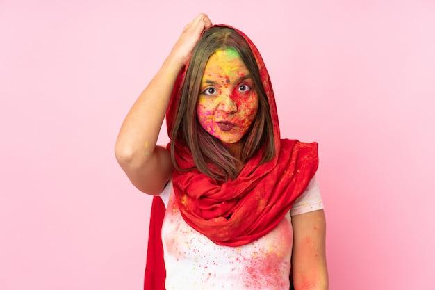 Молодая индийская женщина с красочными порошками холи на лице, изолированные на розовой стене с выражением разочарования и непонимания