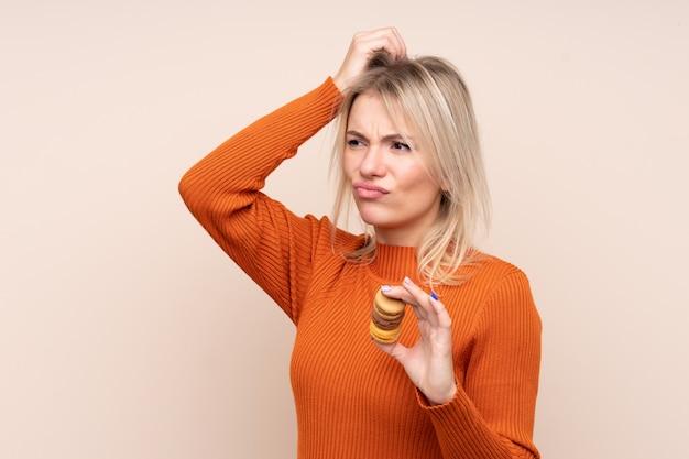 混乱した表情でカラフルなフランスのマカロンを保持している孤立した壁の上の若い金髪ロシア人女性