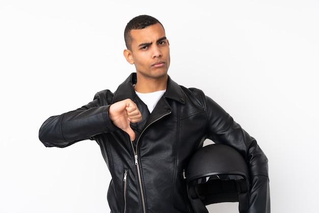 Молодой красавец с мотоциклетным шлемом на белом фоне, показывая большой палец вниз знак