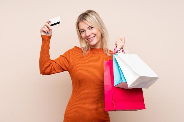 買い物袋とクレジットカードを保持している孤立した壁の上の若いブロンドの女性
