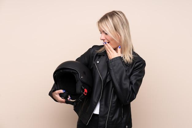 Молодая блондинка с мотоциклетным шлемом над изолированной стеной с удивлением и шокирован выражением лица