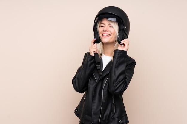 孤立した壁の上のオートバイのヘルメットを持つ若いブロンドの女性