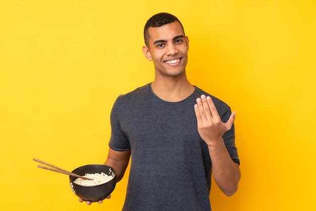 Молодой человек афроамериканца над изолированной желтой стеной приглашая прийти с рукой. рад, что вы пришли, держа миску лапши с палочками для еды