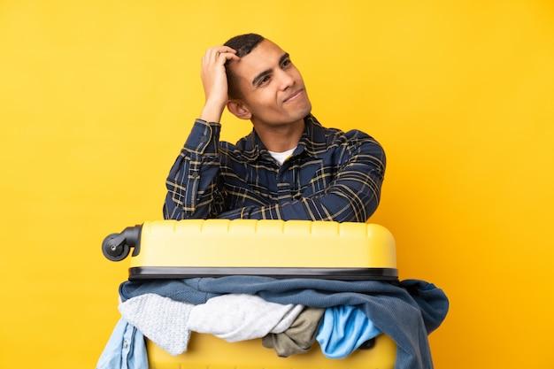 疑問を持って分離された黄色の壁の上の服の完全なスーツケースと混乱の表情を持つ旅行者男