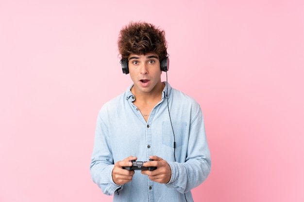ビデオゲームで遊ぶ孤立したピンクの壁の上の若い白人男