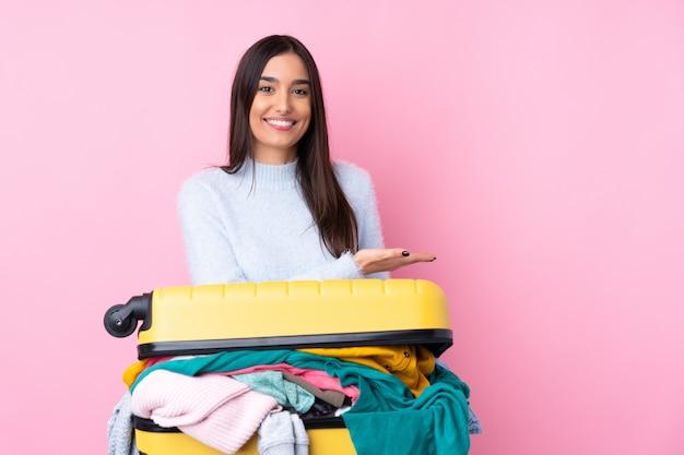 Путешественница с чемоданом, полным одежды, на изолированной розовой стене, протягивающей руки в сторону для приглашения прийти