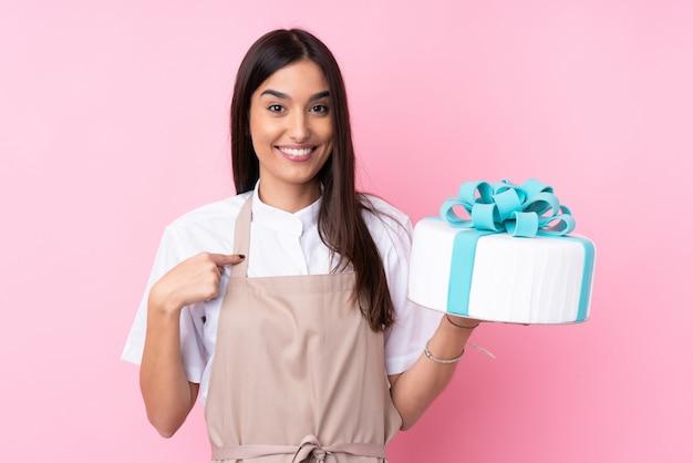 Молодая женщина с большим тортом на изолированной стене с удивленным выражением лица