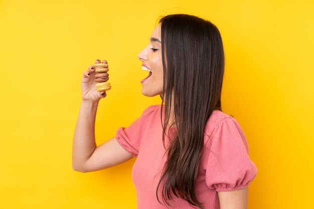 Молодая брюнетка над изолированной желтой стеной, держащей разноцветные французские макаруны