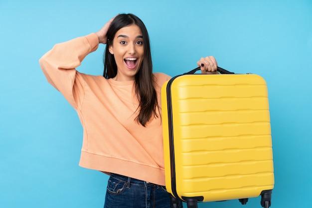 旅行スーツケースと休暇で孤立した青い壁の上の若いブルネットの女性と驚いた