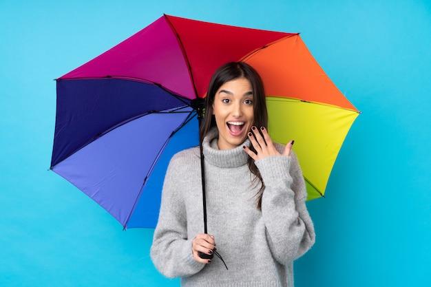 Молодая брюнетка женщина держит зонтик над синей стеной с удивленным выражением лица