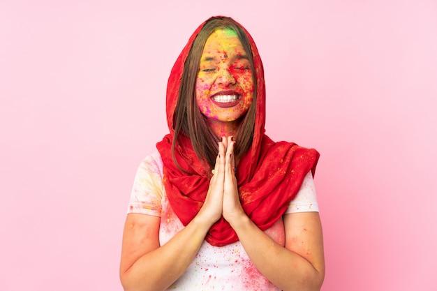 ピンクの壁に分離された彼女の顔にカラフルなホーリーパウダーを持つ若いインド人女性は、手のひらを一緒に保ちます。人は何かを求めます