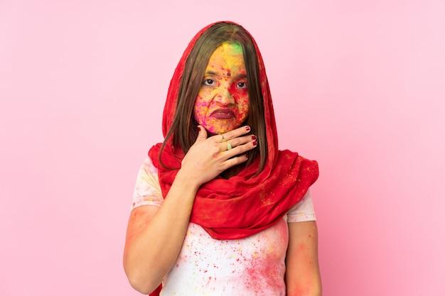 疑問を持つピンクの壁に分離された彼女の顔にカラフルなホーリーパウダーを持つ若いインド人女性