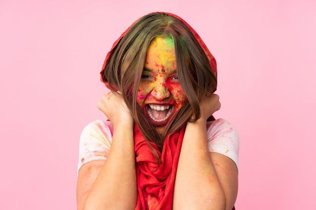 ピンクの壁に分離された彼女の顔にカラフルなホーリーパウダーを持つ若いインド人女性