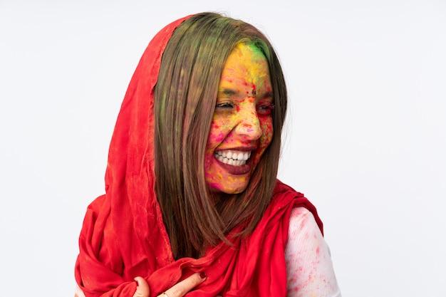 白い壁に分離された彼女の顔にカラフルなホーリーパウダーを持つ若いインド人女性