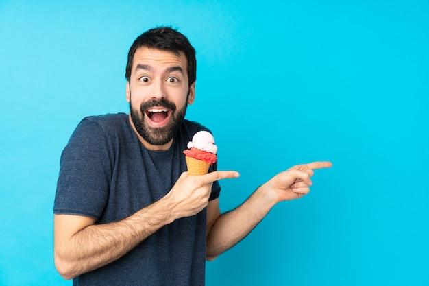 孤立した青い壁の上のコルネットアイスクリームと若い男が驚いて、ポインティング側