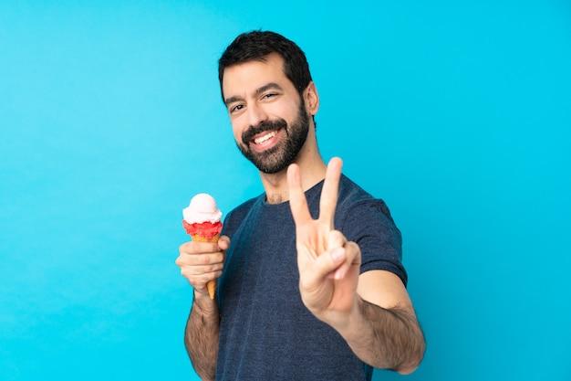 Молодой человек с мороженым корнет над синей стеной улыбается и показывает знак победы