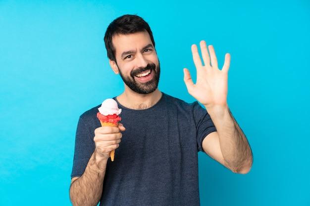 幸せな表情で手で敬礼分離の青い壁の上のコルネットアイスクリームと若い男