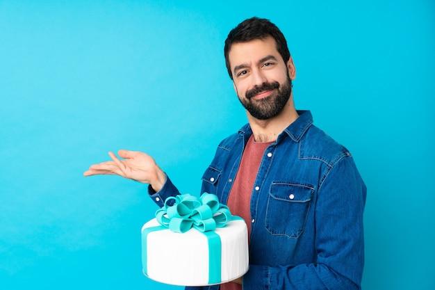 Молодой красавец с большой торт над синей стеной, протягивая руки в сторону за приглашение прийти