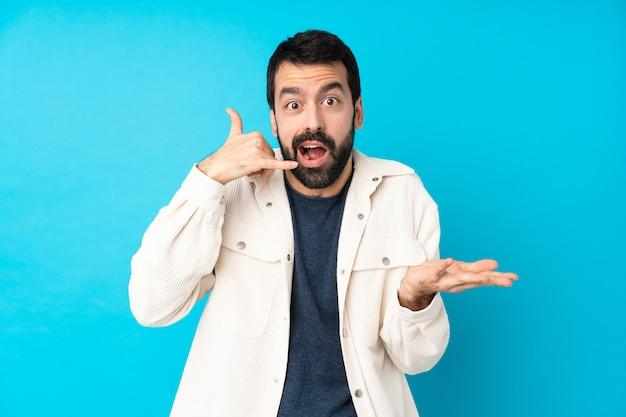 電話ジェスチャーを作ると疑う分離の青い壁の上の白いコーデュロイジャケットと若いハンサムな男