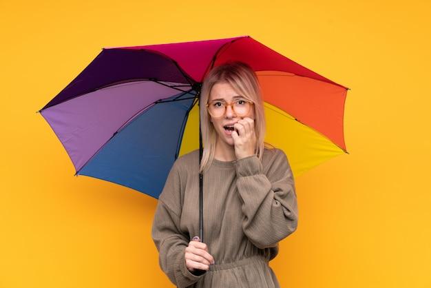孤立した黄色の壁に傘をかざす若いブロンドの女性神経質と怖い