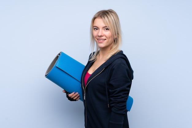 マットと笑みを浮かべて分離の青い壁の上の若いスポーツブロンドの女性