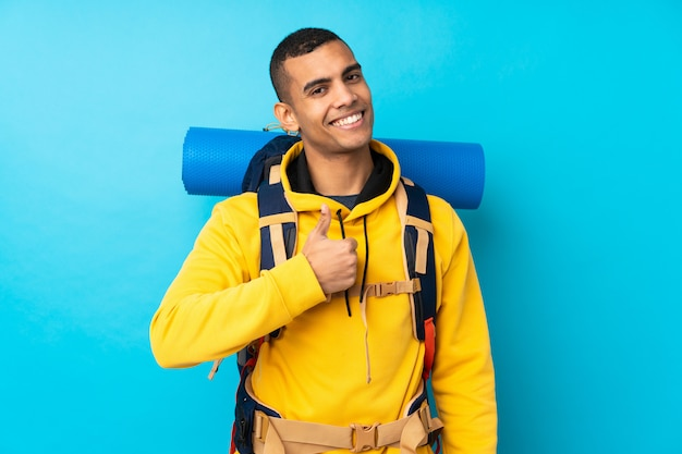 親指ジェスチャーを与える分離の青い壁の上の大きなバックパックを持つ若い登山家男