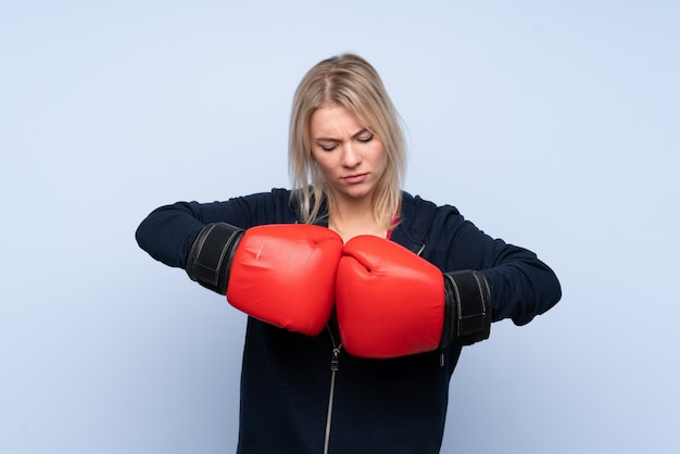 ボクシンググローブと分離の青い壁の上の若いスポーツブロンドの女性