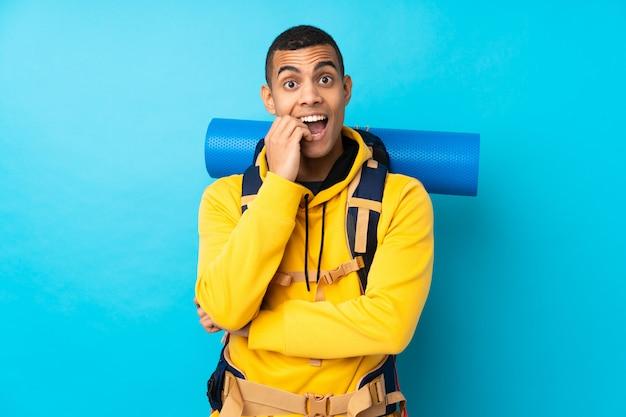 Молодой альпинист человек с большим рюкзаком над синей стеной нервной и страшно