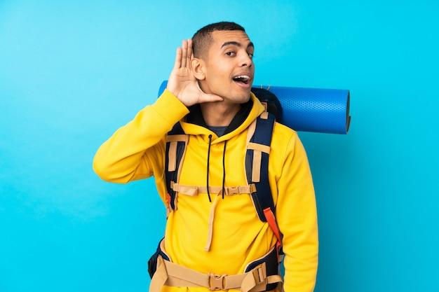 Молодой человек альпиниста с большим рюкзаком над синей стеной, слушая что-то