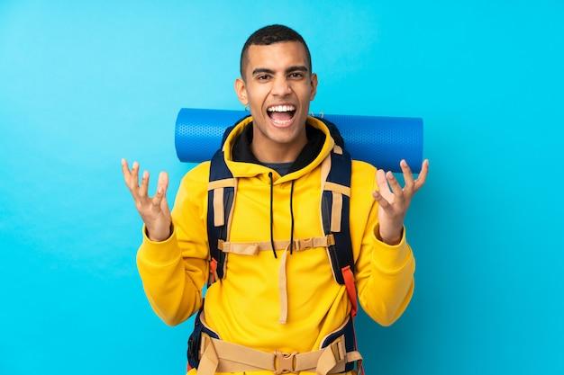不満と何かに不満の孤立した青い壁の上の大きなバックパックを持つ若い登山家男