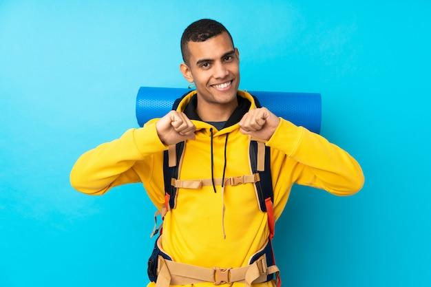 孤立した青い壁の誇りと自己満足の上の大きなバックパックを持つ若い登山家男