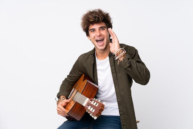 口を大きく開けて叫んで孤立した白い壁にギターを持つ若い白人男