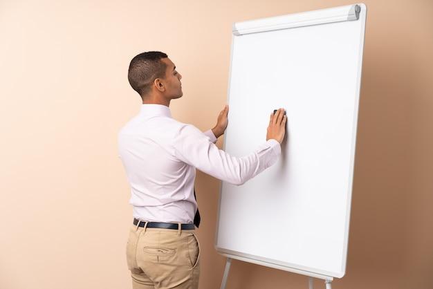 Молодой деловой человек на изолированной стене, давая представление на белой доске и писать в нем